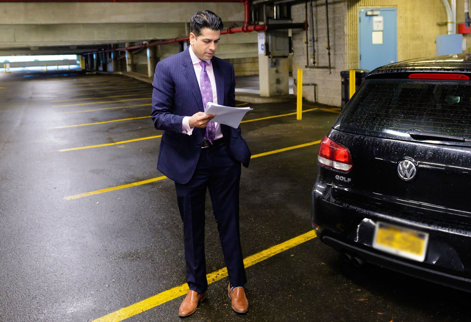 Man in striped blue shirt, pink shirt, and purple graphic tie stands next to his car in an empty parking garage and reviews papers in his hand.