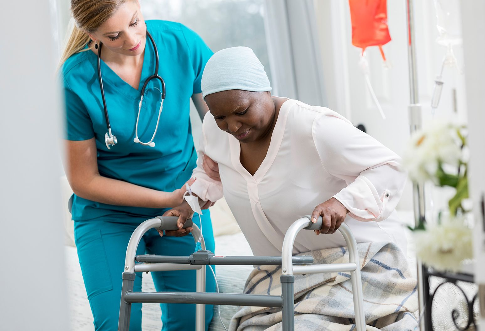 Senior African American female patient uses a walker in her home. A home healthcare nurse is assisting her.