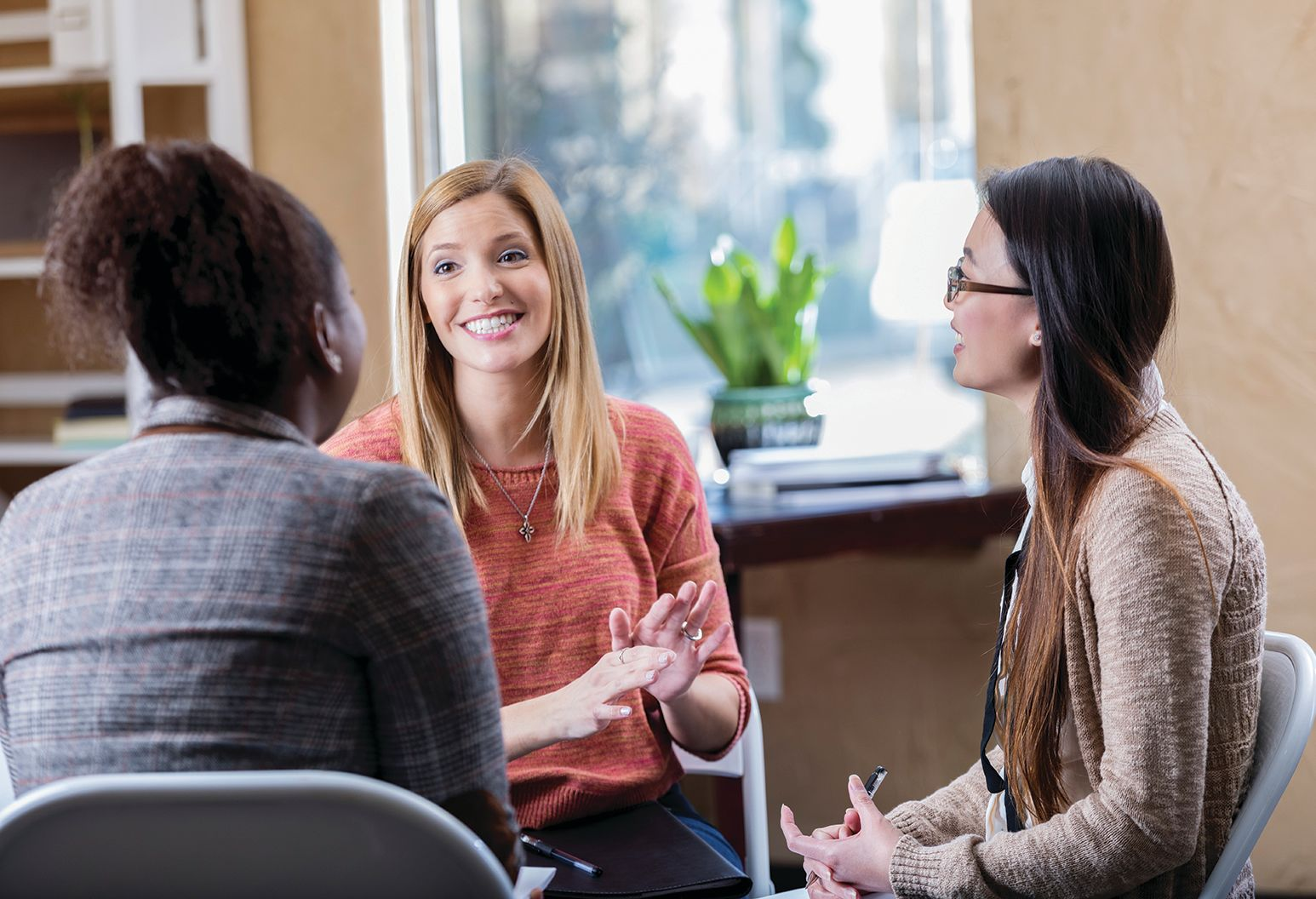 Beautiful mid adult Caucasian woman shares emotions during group therapy session. She is talking with mid adult African American woman and young Asian woman.
