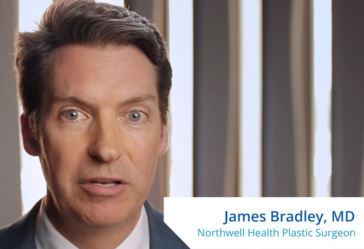 "A man with brown hair and blue eyes speaks to the camera. On the lower right corner of the photo it reads, ""James Bradley, MD. Northwell Health Plastic Surgeon."""