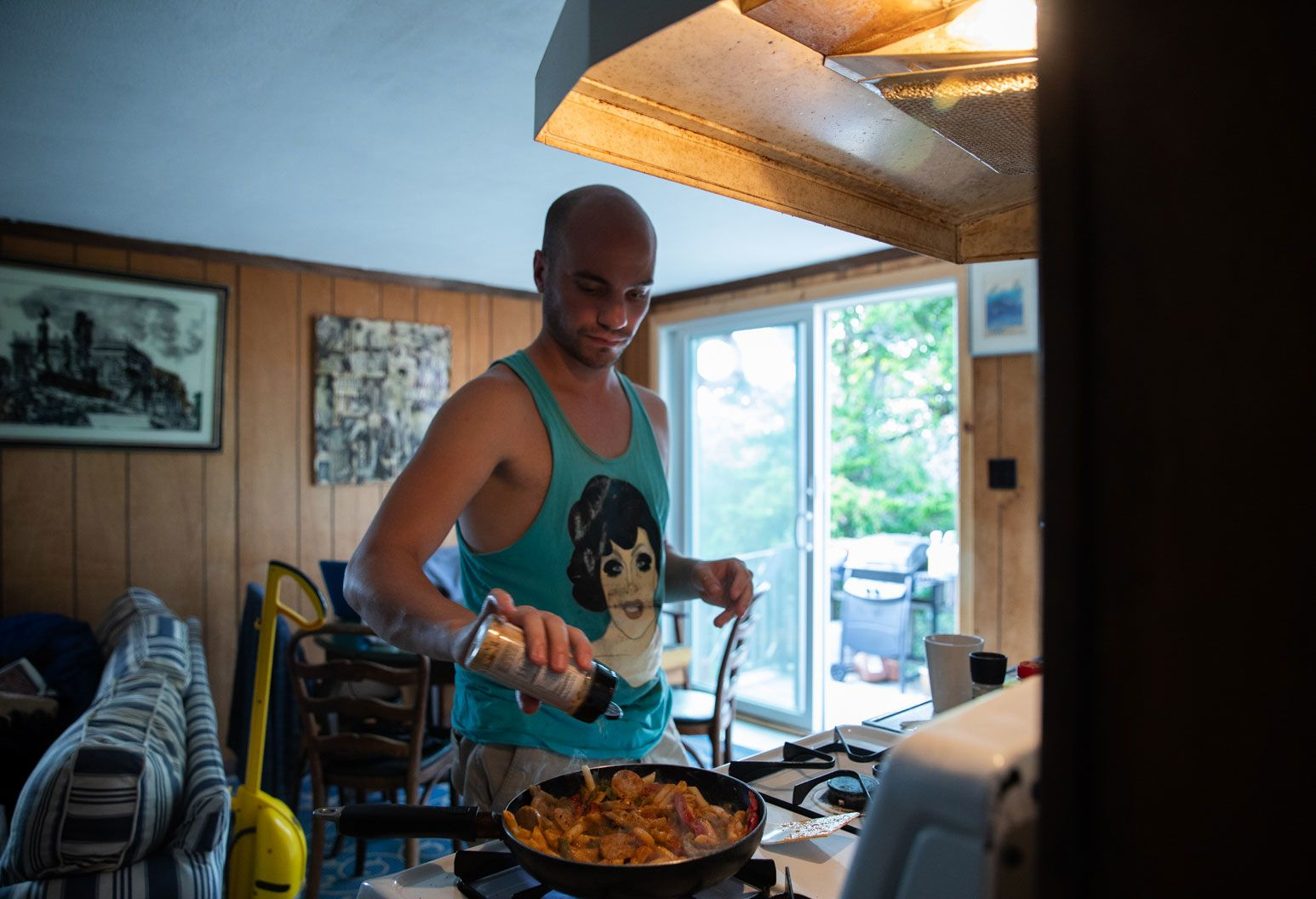 A bald man in a blue tank top pours seasoning over a plate of grilled shrimp that is boiling up on a stove in the kitchen.