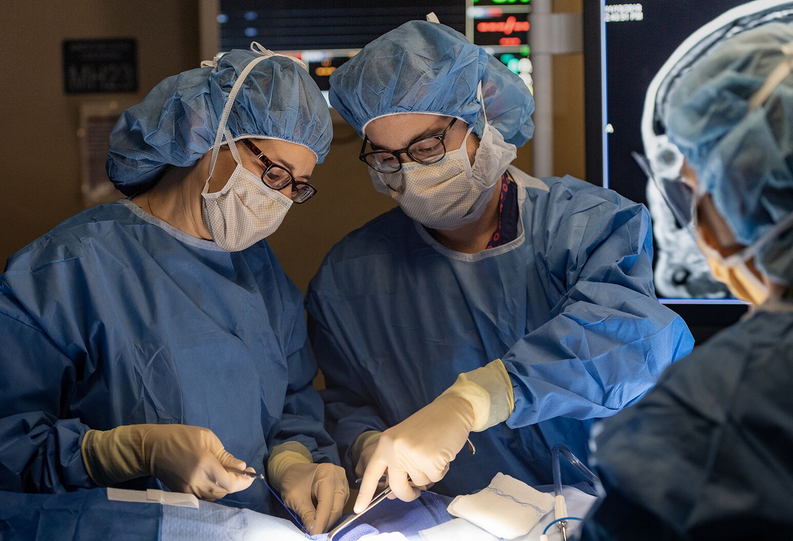 Two physicians in full blue scrubs performing surgery