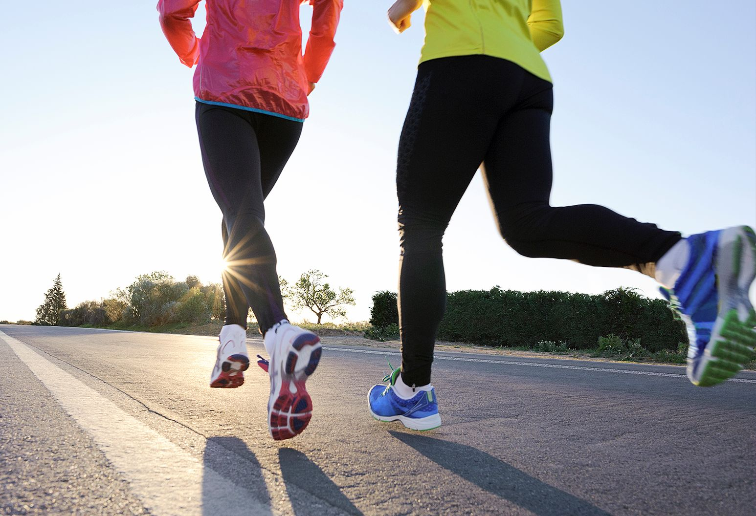 Two athletes running down a long two lane highway as the sun starts to set in the background