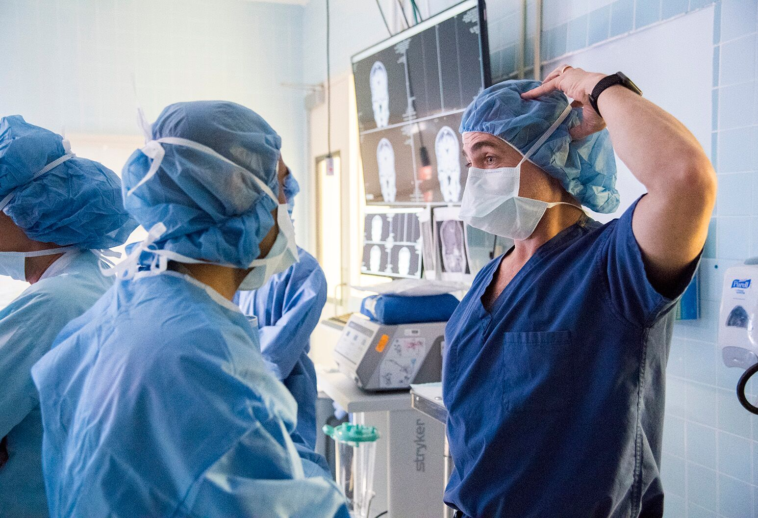 Doctors in operating room fixing scrubs.