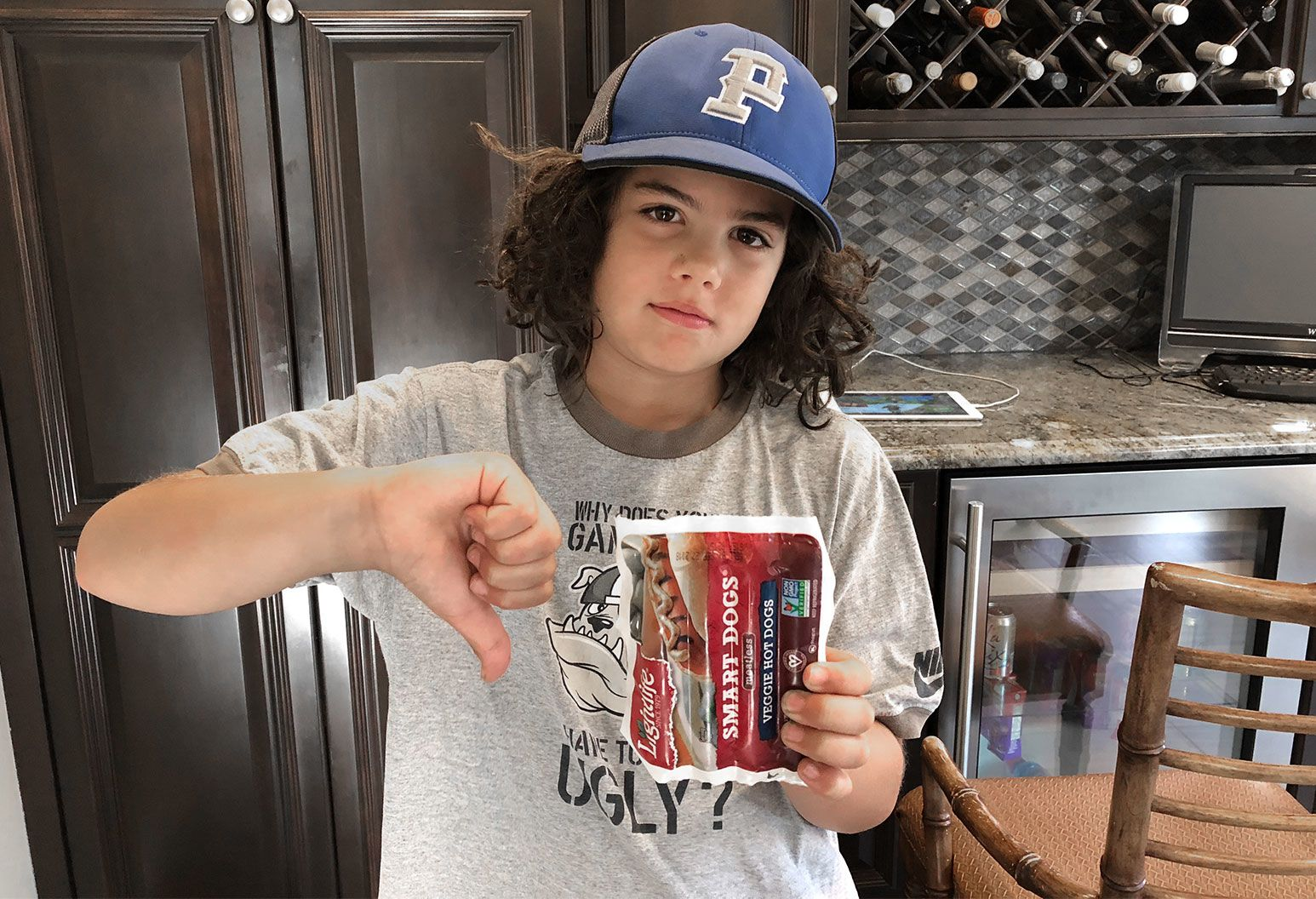A teen boy with long black hair and a cap stands in a kitchen giving a thumbs down with one hand and an image of a hot dog on the other.