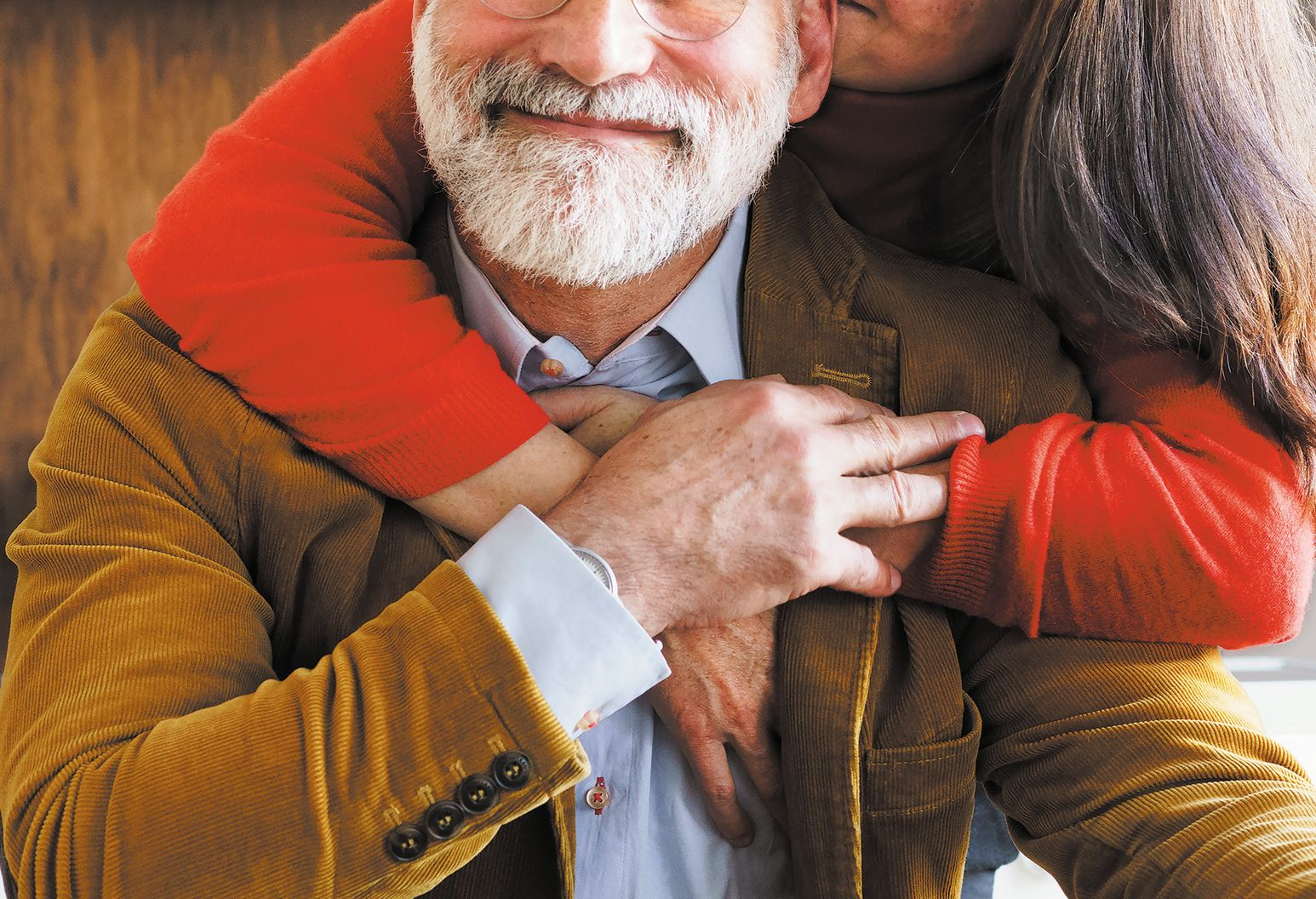 A woman in a red sweater hugs a man in a brown corduroy jacket, who smiles at the camera.