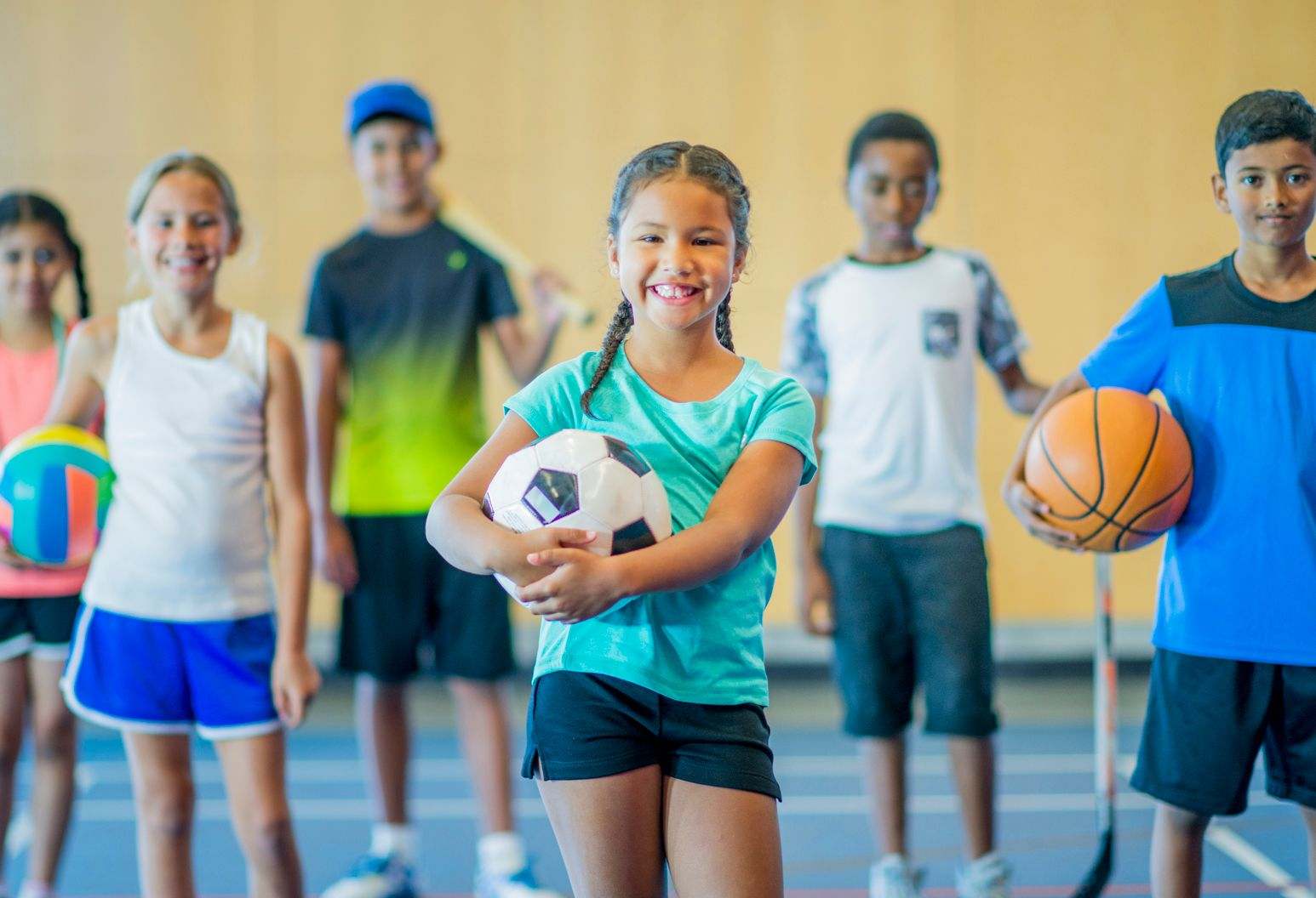 A multi-ethnic group of kids are standing in a gymnasium. They are holding a basketball, volleyball, hockey stick, skipping rope, baseball bat, and soccer ball. They are smiling.