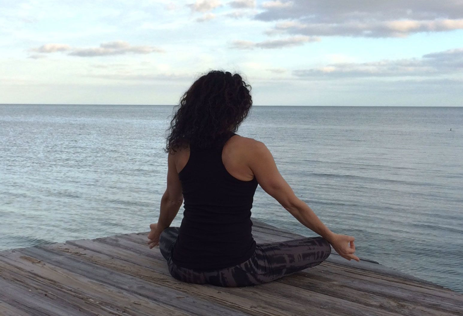 A woman sits on a wooden pier by the water. Her back towards the camera, she sits in a meditative position with her hands stretched to her knees as her black hair flows in the wind.