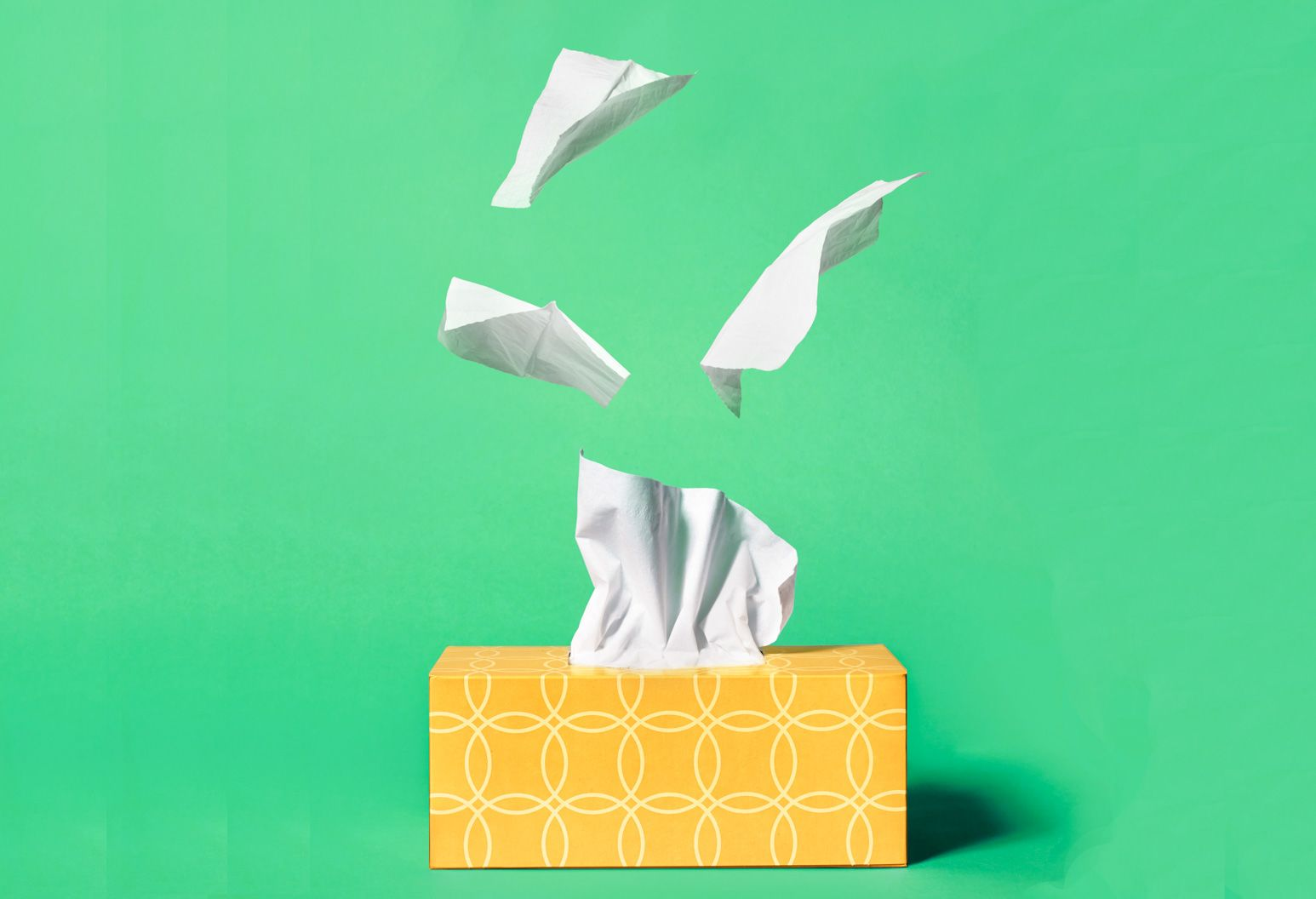 A yellow box of tissues sits in front of a kelly green background. Tissues are flying out of the box.