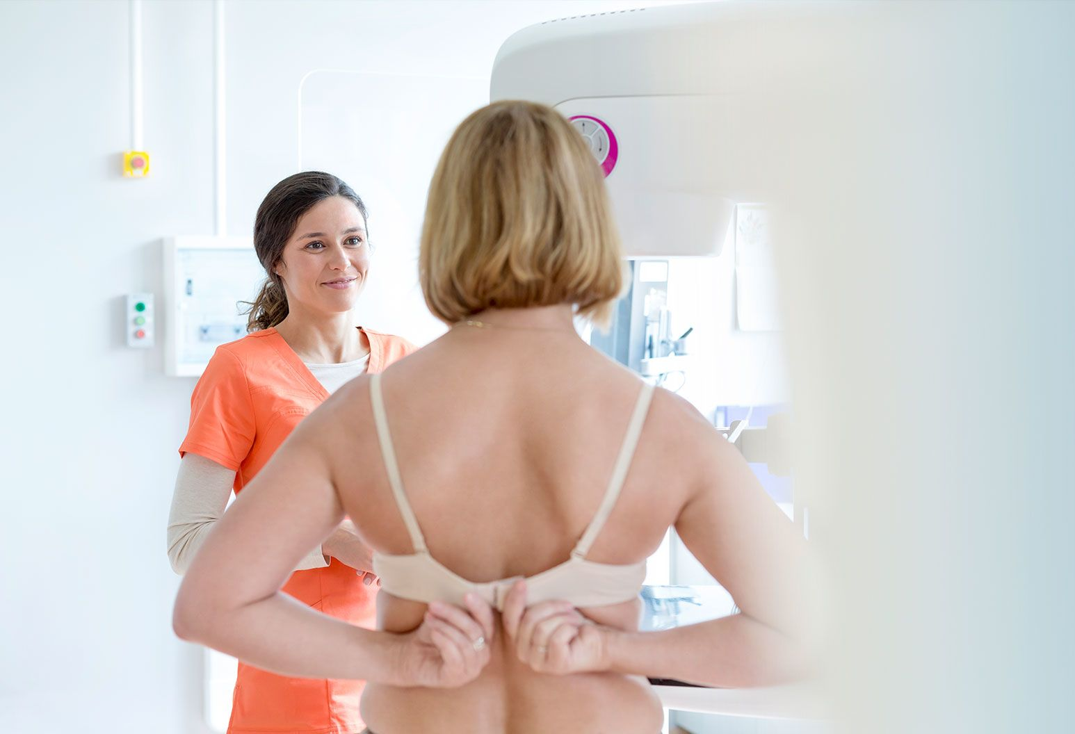 A blonde woman, unhooks her bra as she faces another female in an orange work outfit. The female gives a comforting smile to the woman who is standing in front of a mammogram imaging machine.