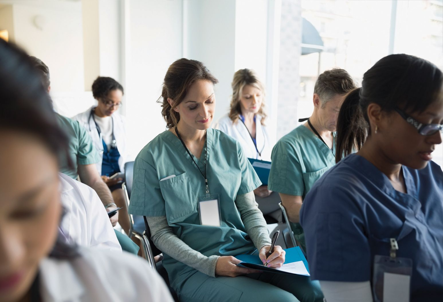 Young woman in green scrubs sits among other young professionals taking notes.