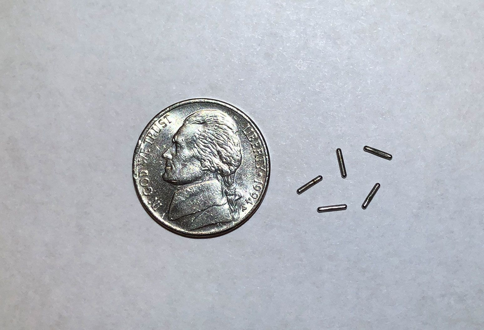 "Brachytherapy ""seeds"" - An aged silver 5 cent nickel is resting on a table next to smaller thin pieces of metal rods. They are shaped like vertical ""seeds""."