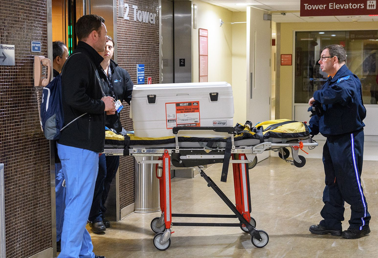 Several people wheel a gurney out of an elevator. On the gurney sits a white cooler with a sticker that says heart on it. They are in the hallway of a hospital.