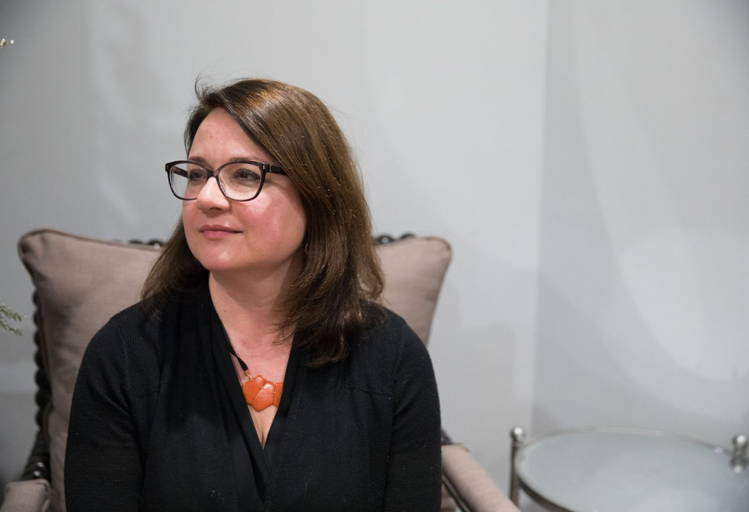 A woman with shoulder length brown hair wears glasses. She wears a black shirt and orange necklace. She is sitting on a grey chair with a pillow behind her.