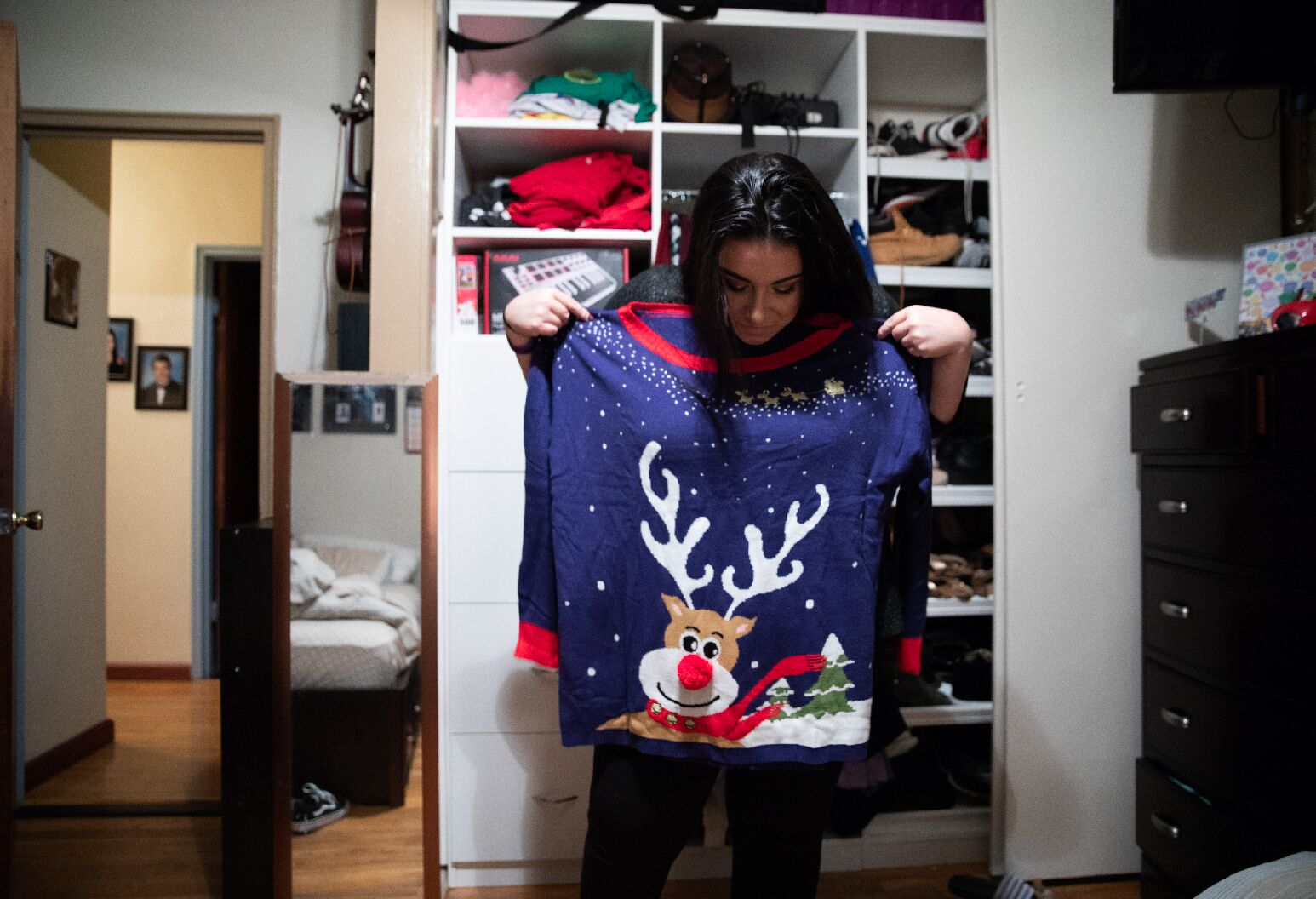 Woman holding up Christmas themed sweater to her body