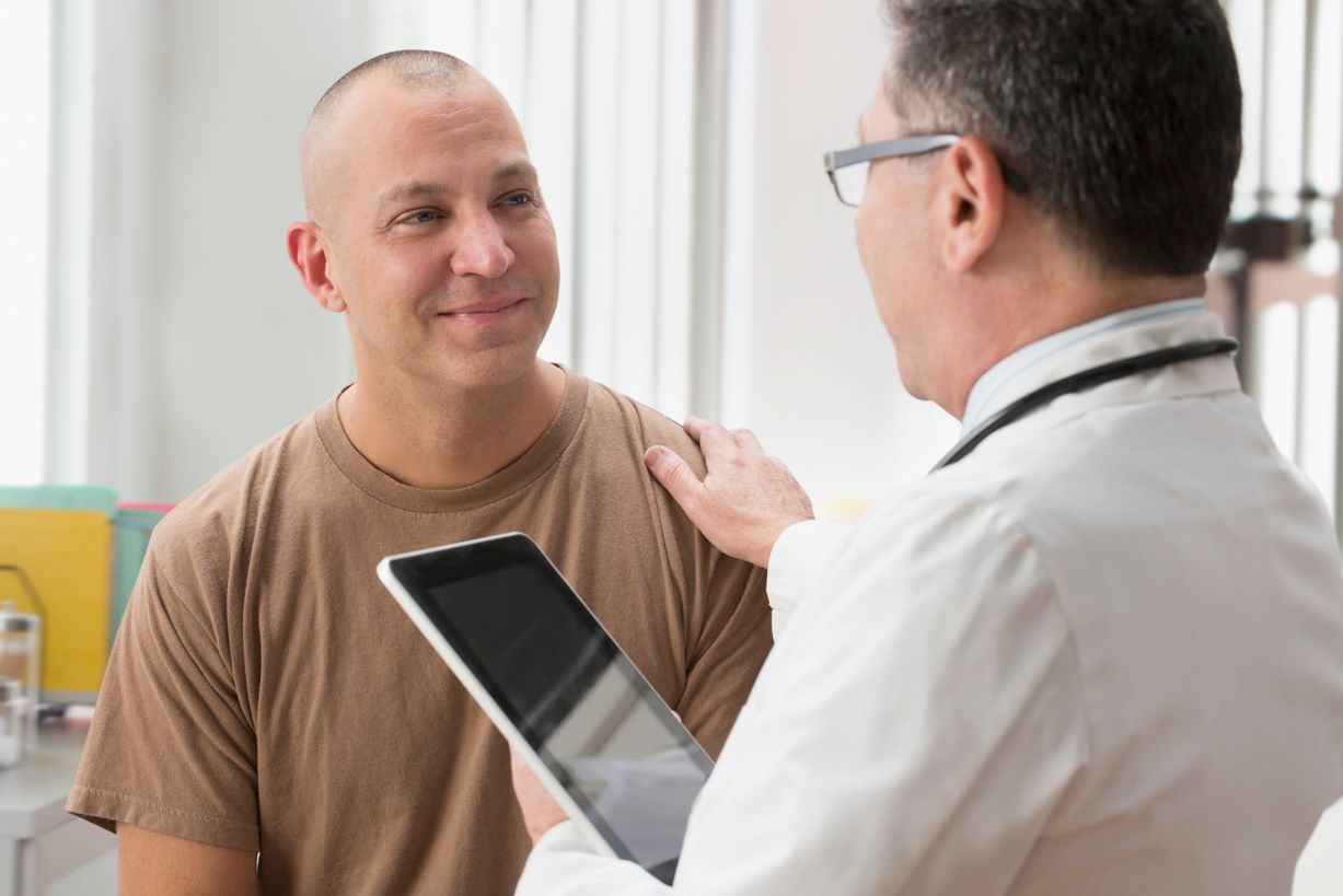 A male doctor holds his hand on a male patient's shoulder