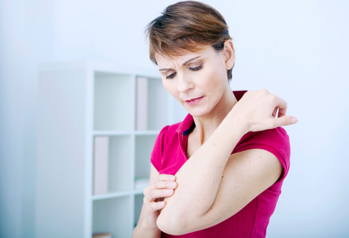 A woman holds her elbow