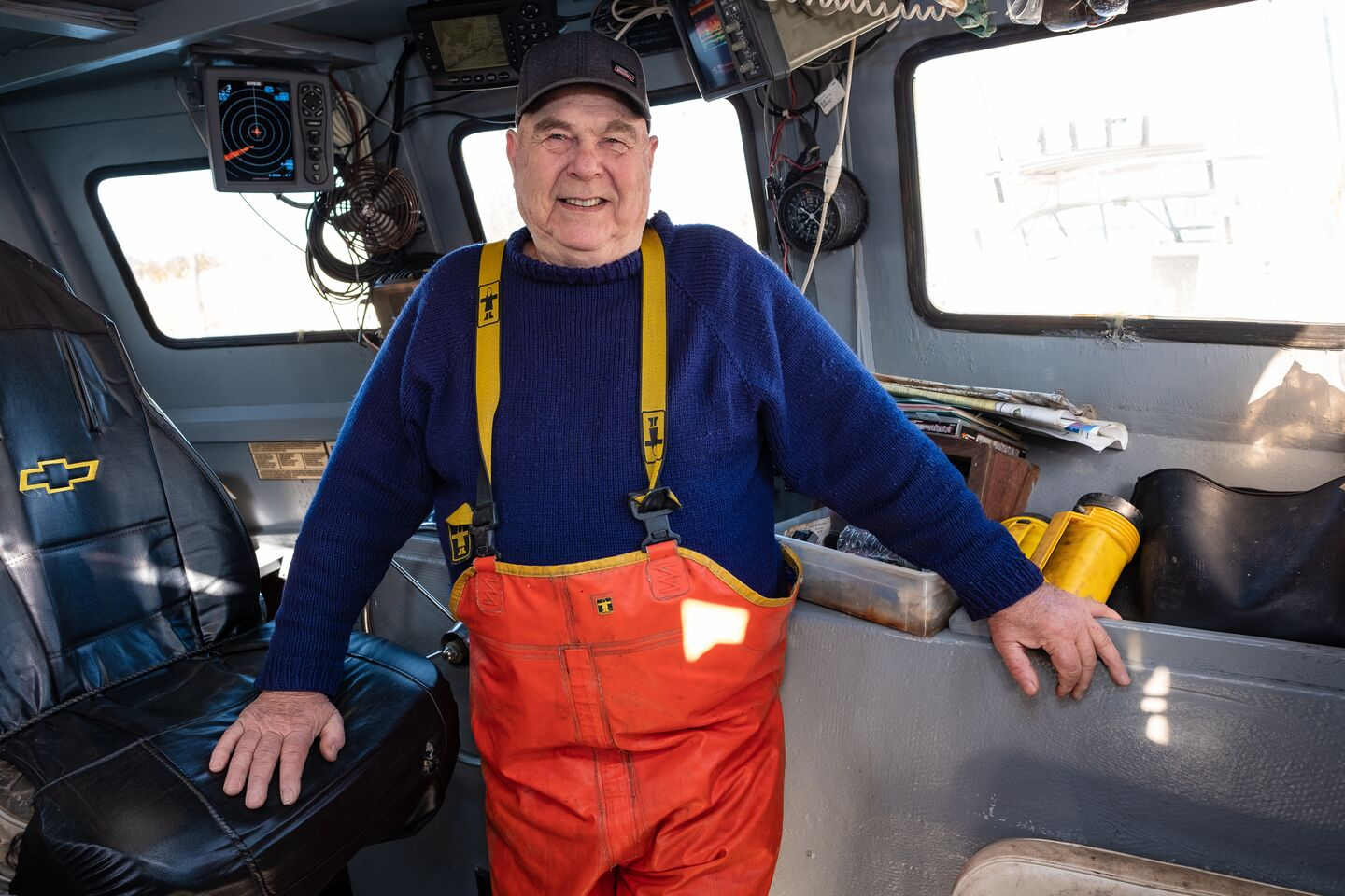 A fisherman in his 70s stops for a smile while below deck on a commercial fishing boat.