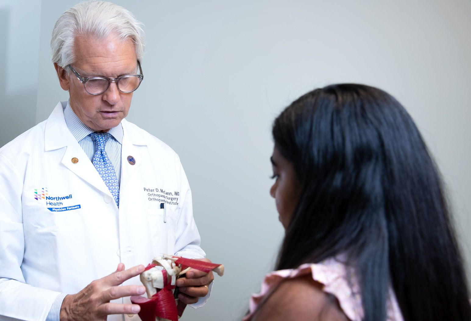 A male doctor wearing a white coat and blue glasses shows a joint model to a female patient with long, dark hair.