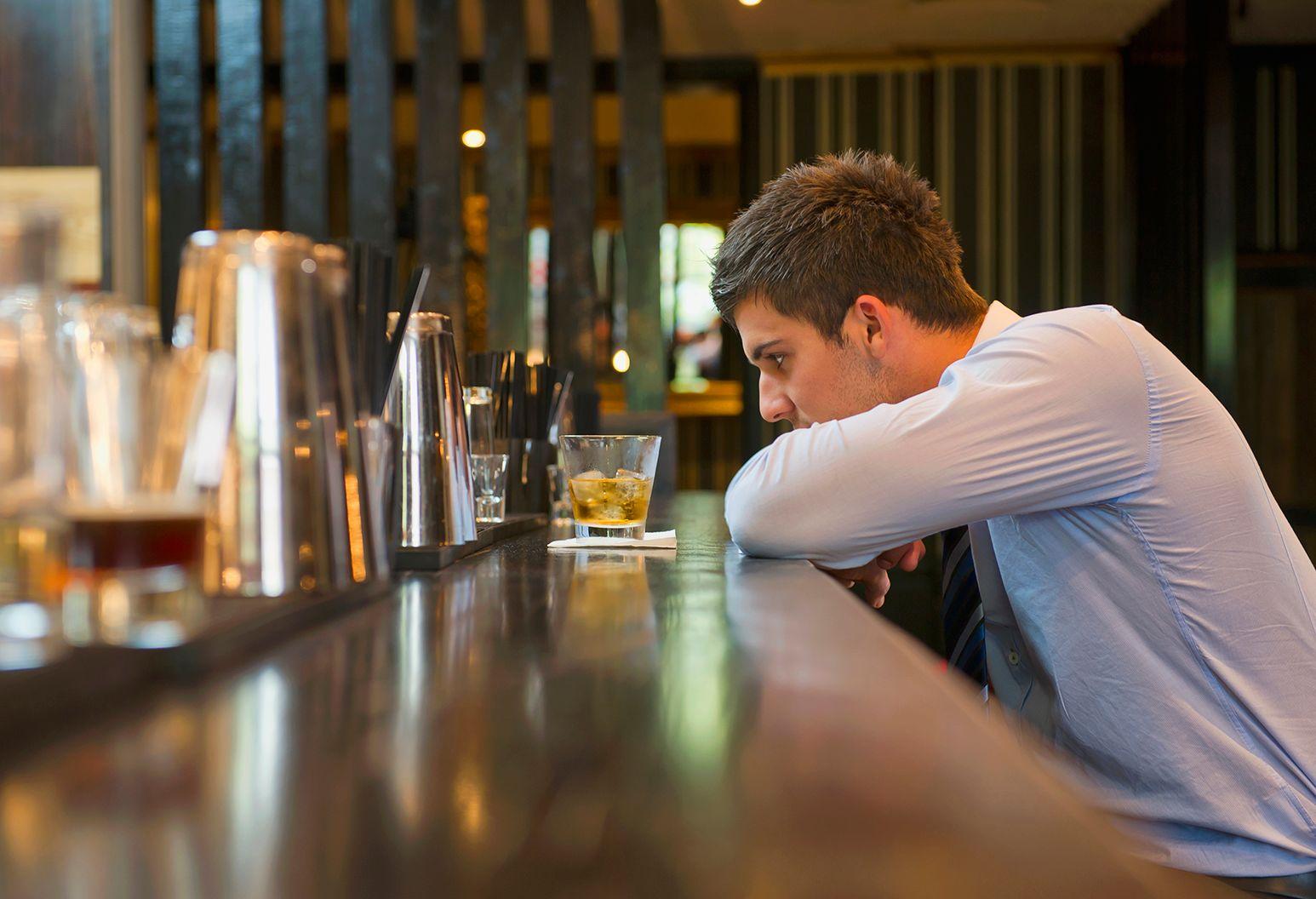 A man contemplates a drink at a bar.