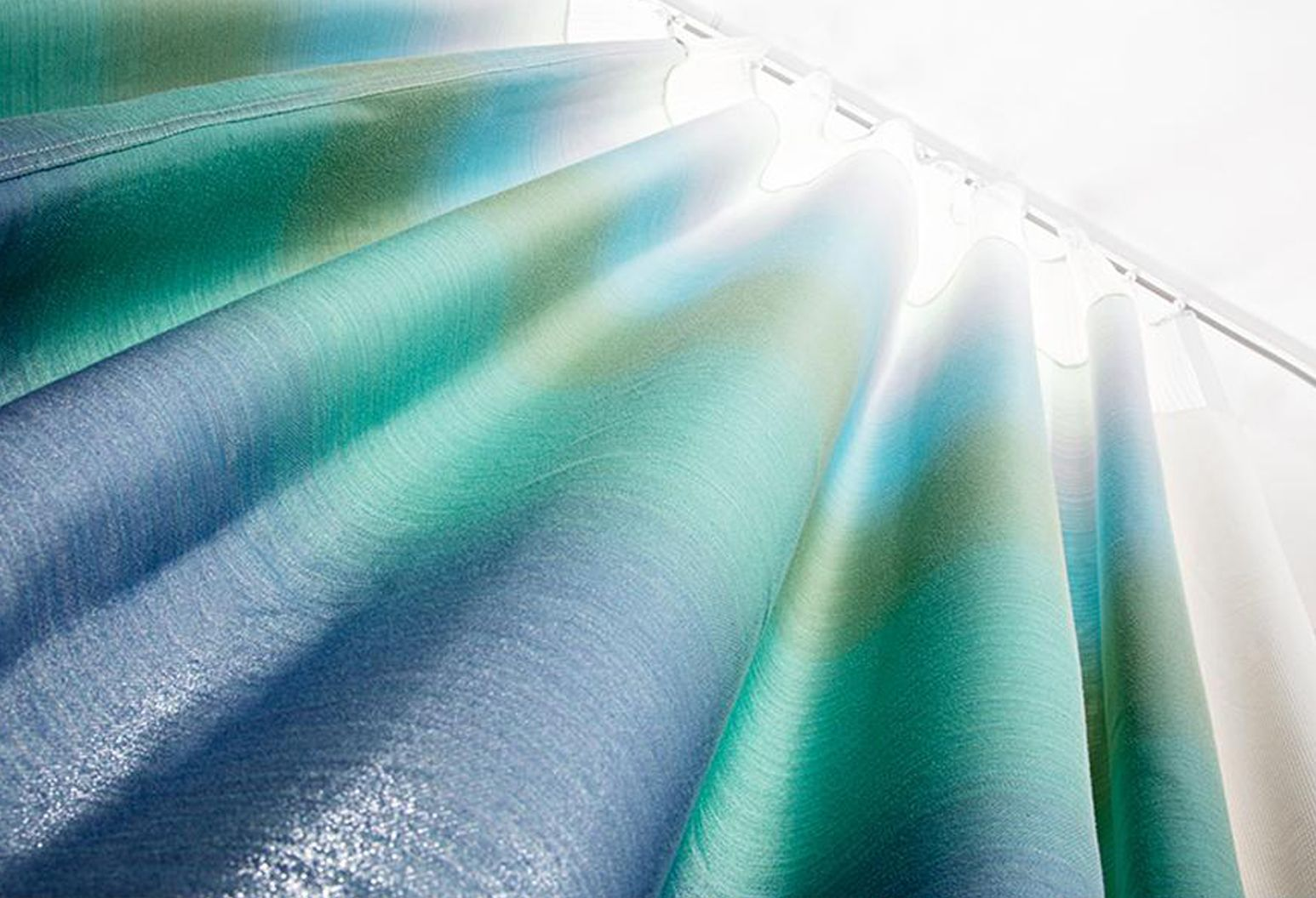Image of a blue green hospital curtain. Viewer is looking up at the curtain and a light is shining down from the top.