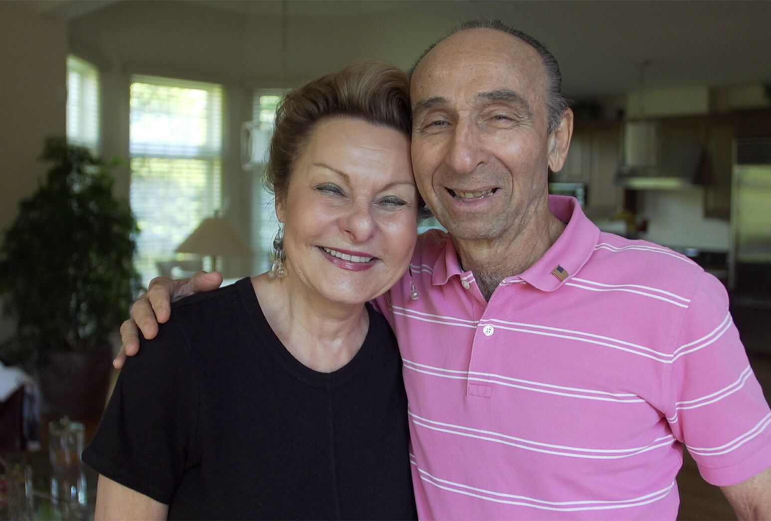 Older couple, woman in a black shirt and man in a pink shirt.