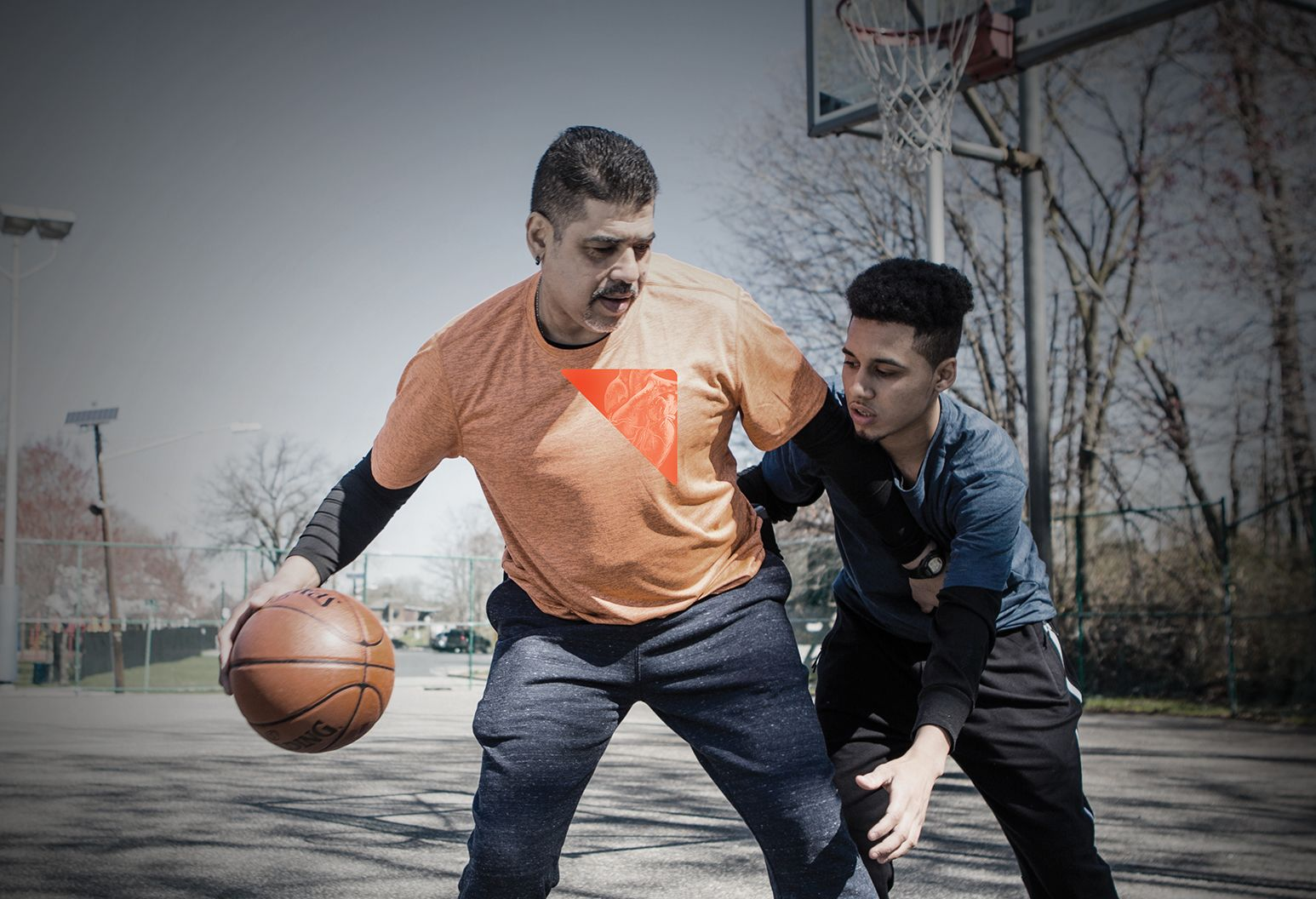A man and a boy play basketball on a court. The man has the ball in his hand and the boy is trying to get the ball. There is an orange constellation over the man's heart.
