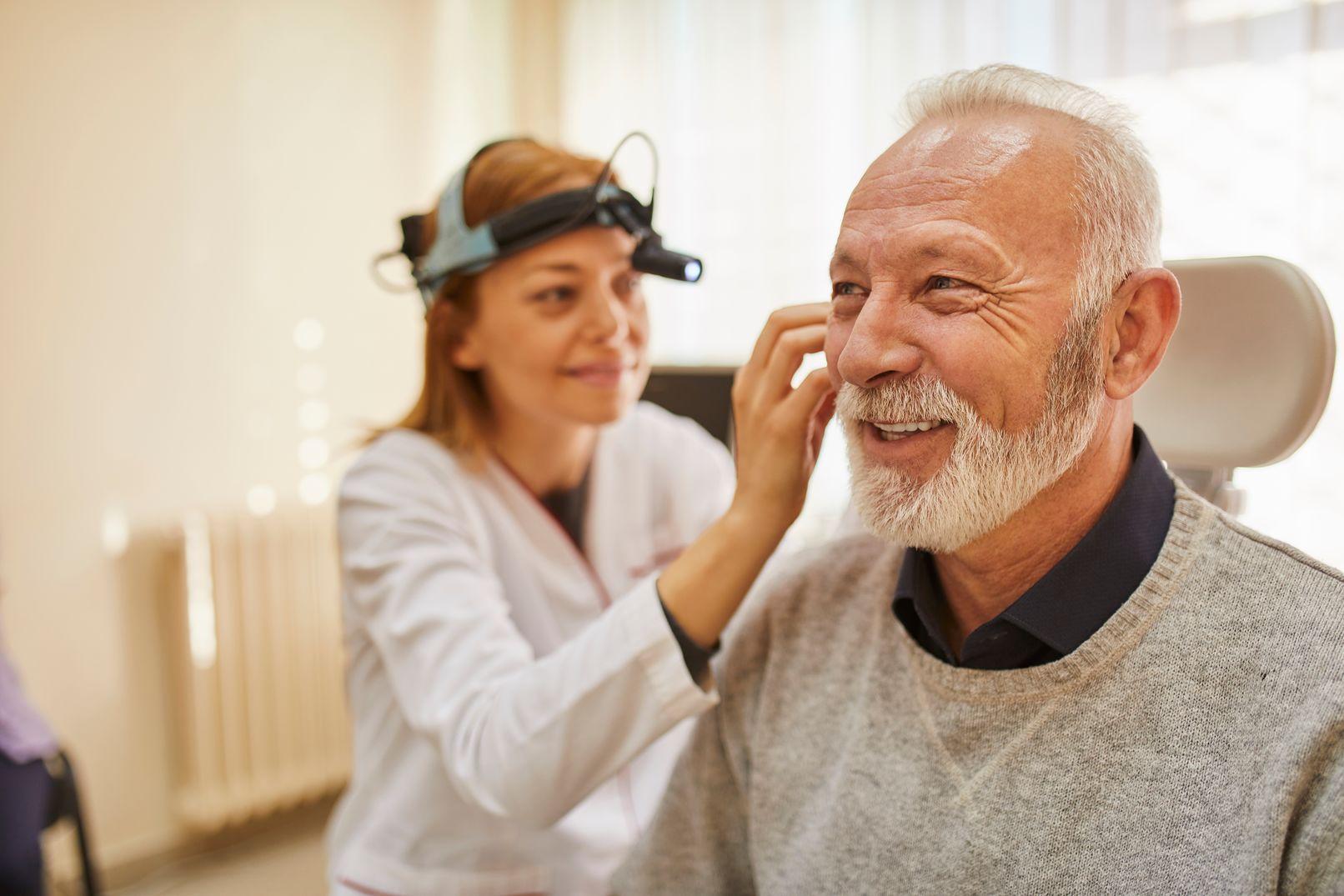 An ENT checks a man's ear