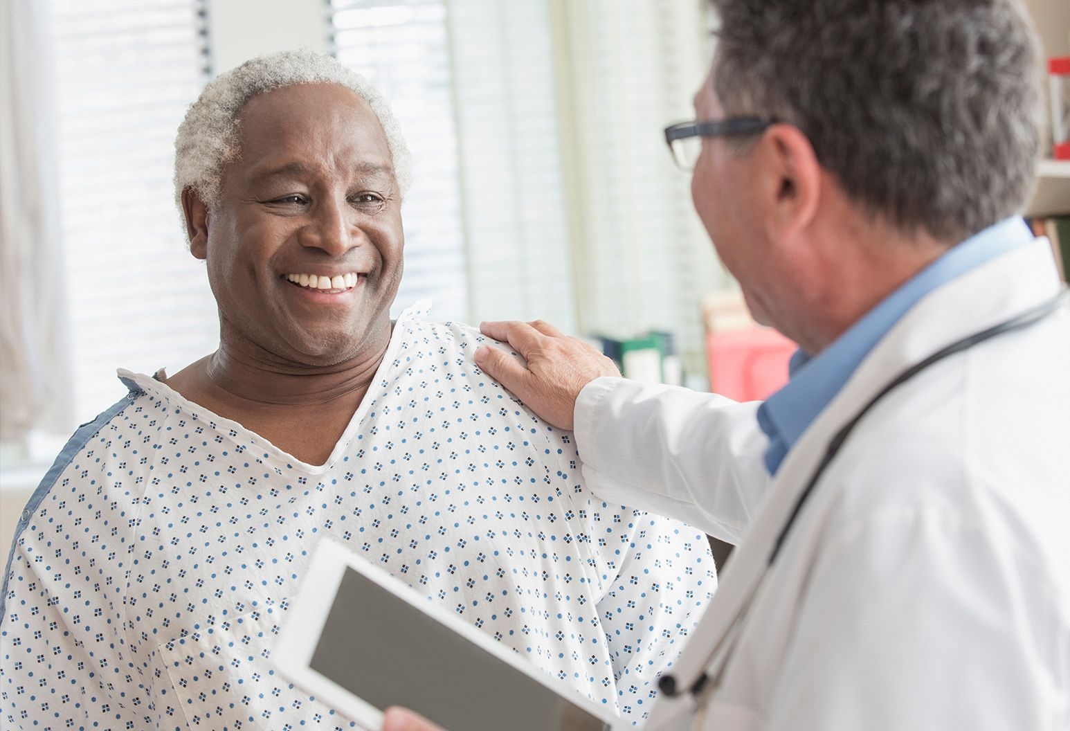 Man smiles as doctor touches his shoulder