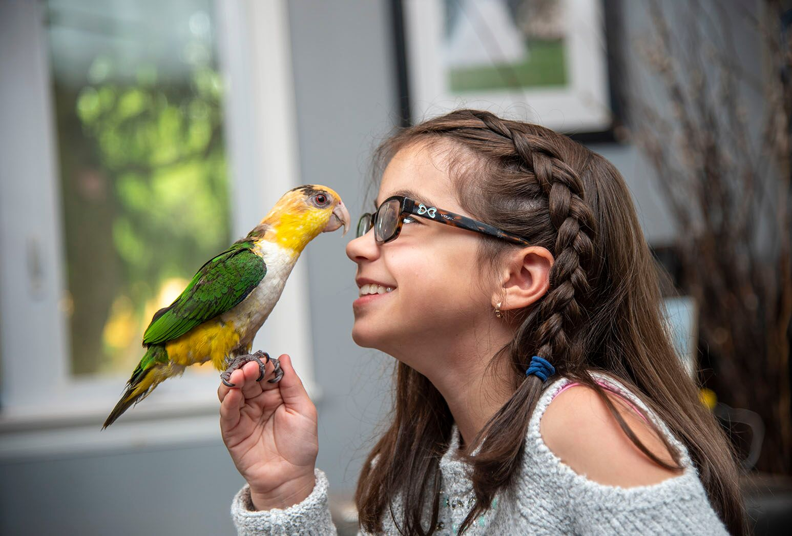 Young girl with brown hair holding a parrot and smiling face to face with it.