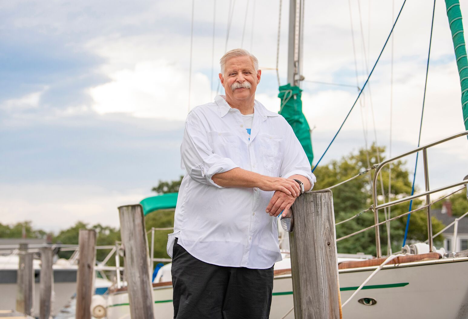 Man in his 60s stands next to a sailboat on an overcast day.