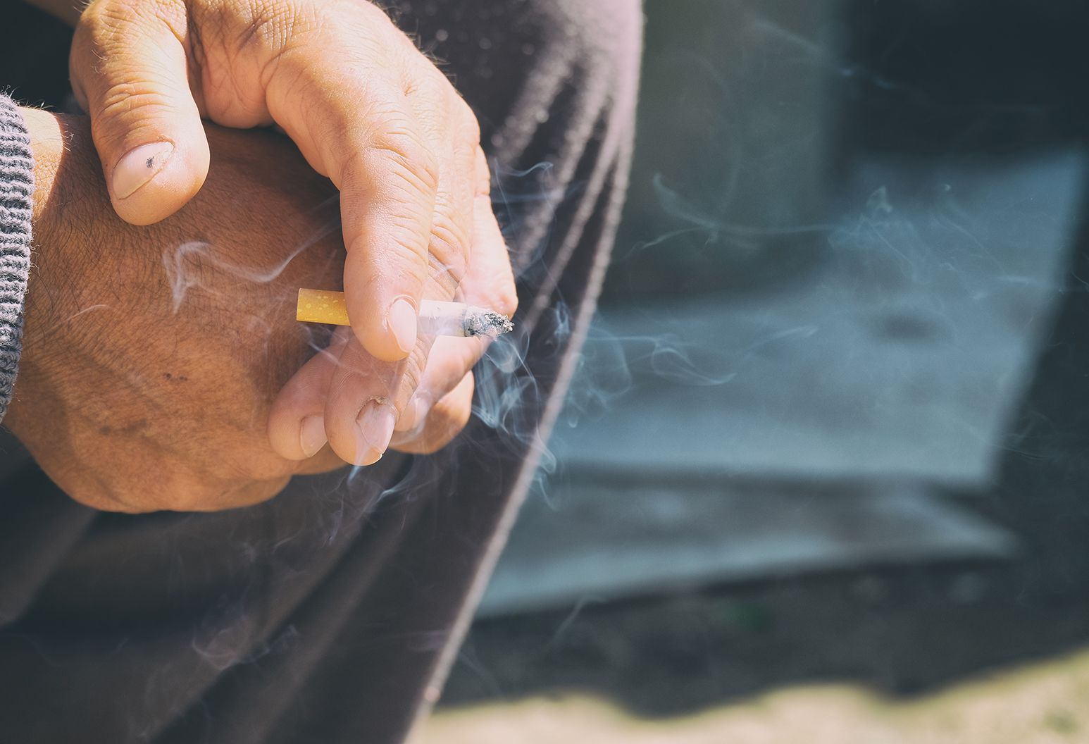 In the upper left hand corner of the photo, we see the hands of an older man. They are folded over each other and in between two fingers is an almost finished cigarette. The smoke from the cigarette curls upwards.