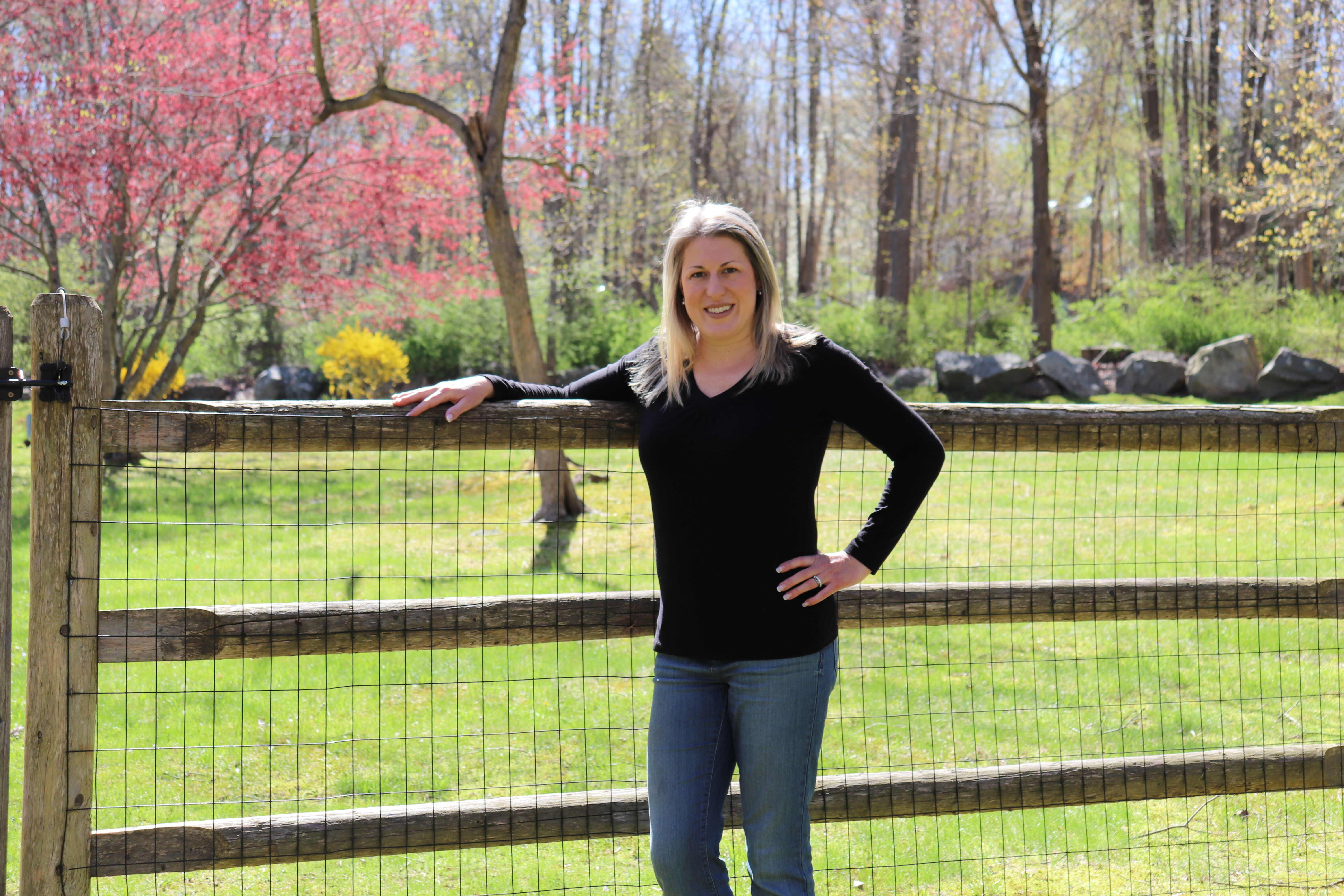 Blond-haired woman in her 40s who had a mommy makeover, dressed in a black long sleeve shirt and blue jeans, leaning on a wooden fence.