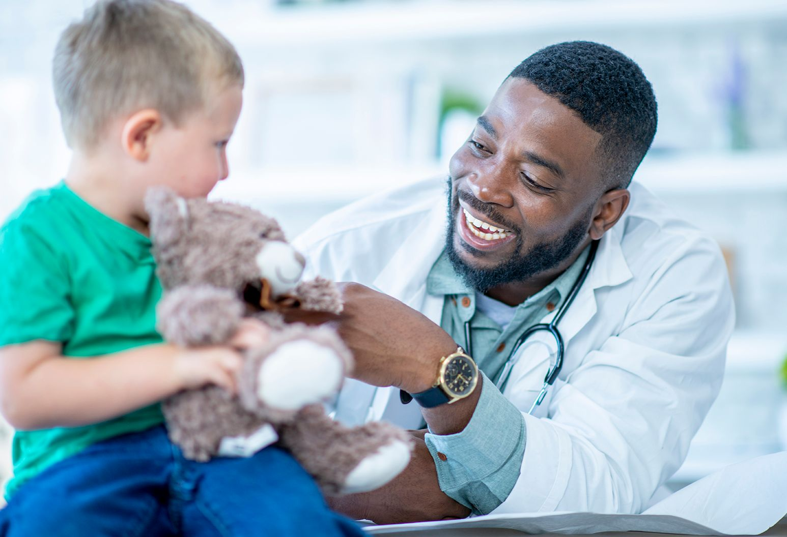A young boy and his doctor are indoors in a hospital. The boy is holding a teddy bear and smiling while talking to his doctor.