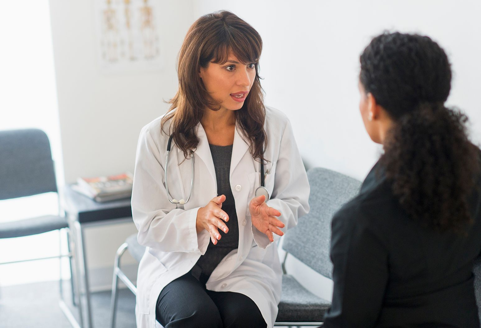 A doctor with long brown hair sitting in the waiting room talking to her patient