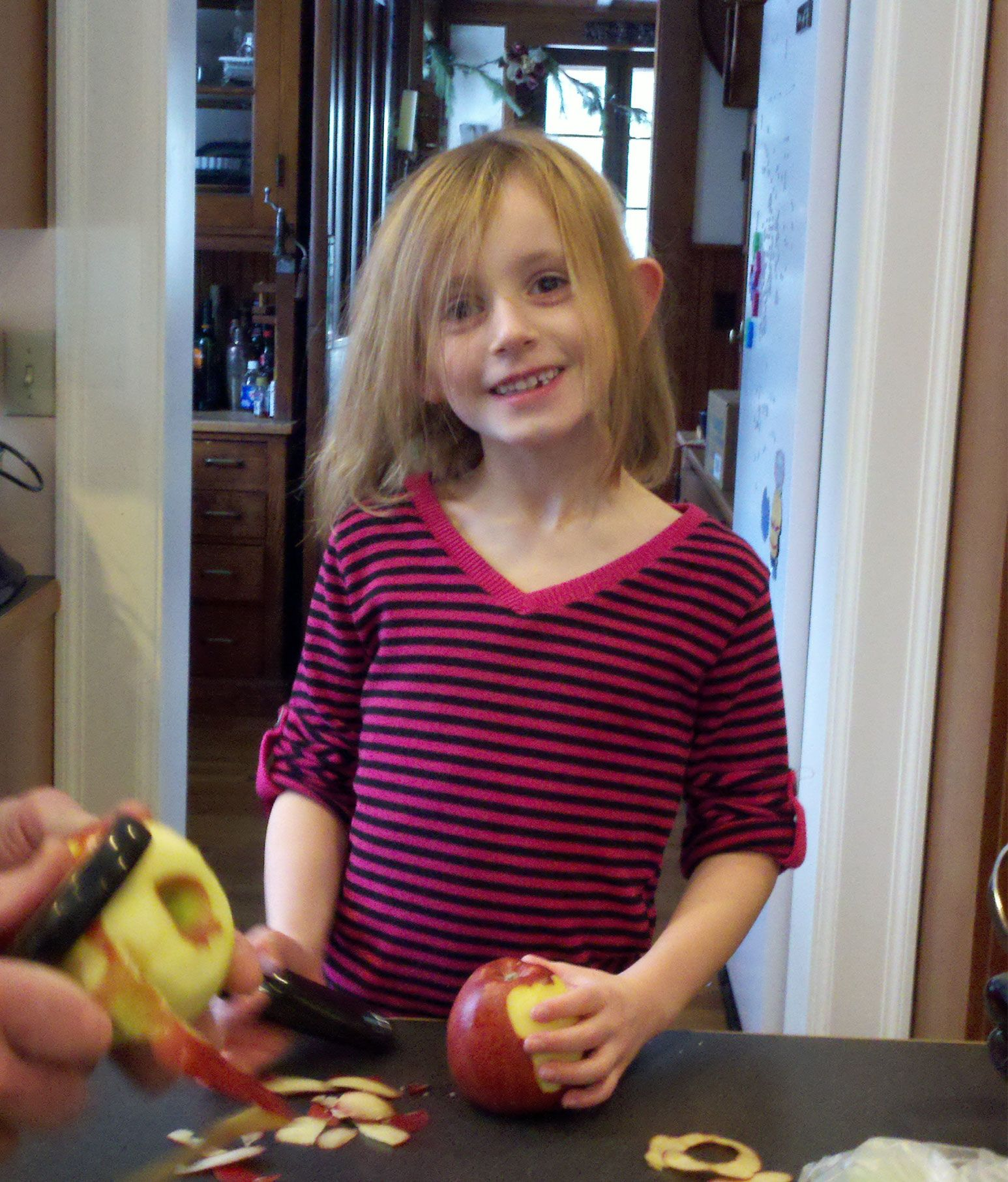A skinny young girl stands in front of a kitchen table smiling as she holds a freshly cut apple.