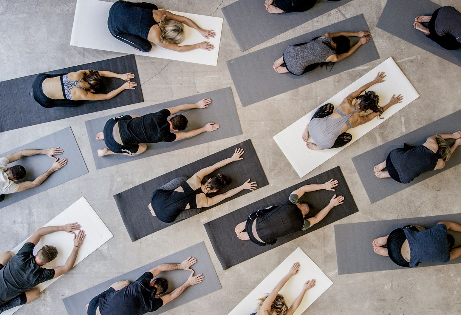 Men and women perform the yoga pose downward dog on black, gray and white yoga mats.