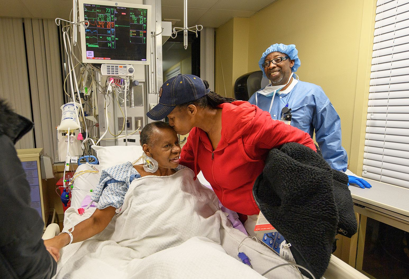 A woman in a blue baseball hat and red sweatshirt kisses a woman sitting in a hospital bed on the forehead. A man in surgical scrubs stands to the side and looks on.