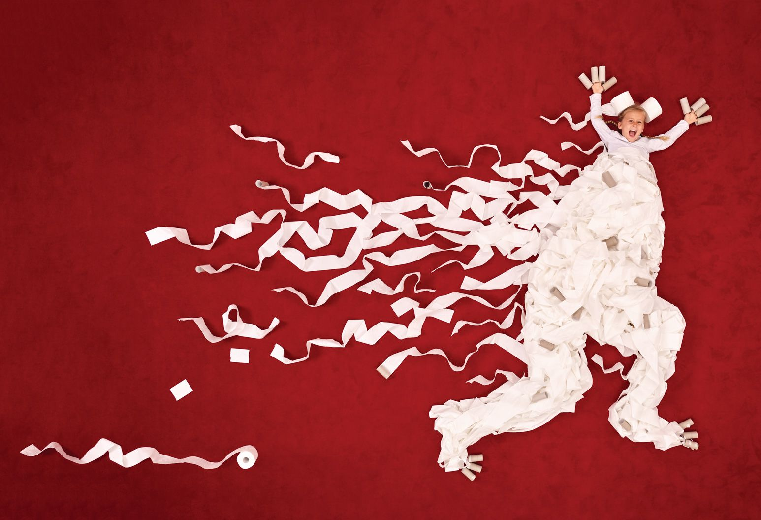 This is an abstract image with the face of a five year old girl with the body of a monster made out of toilet paper. She is running with her arms up as toilet paper trails behind her over a red background.