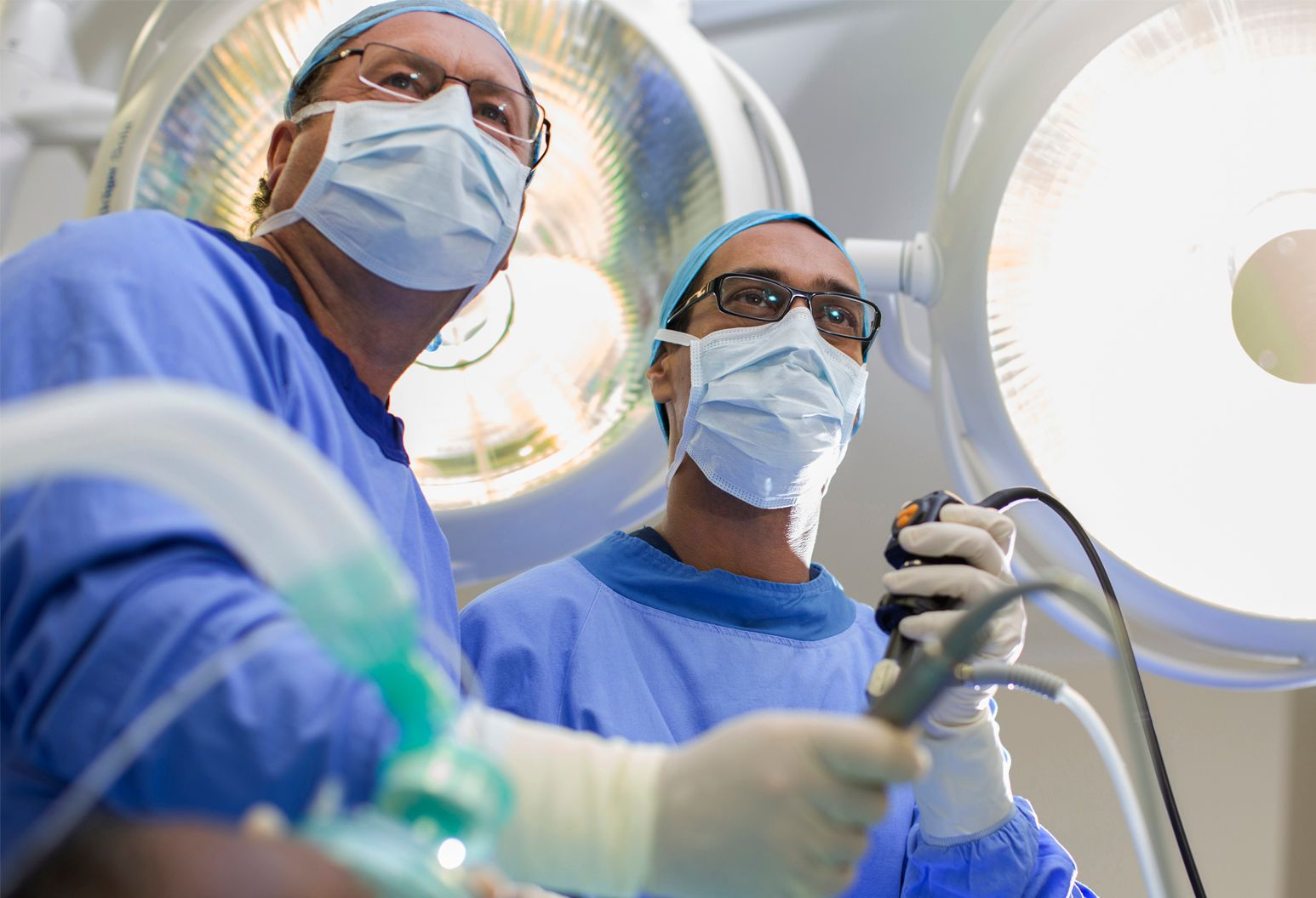 Two male physicians in surgical gear operating with robotic technology