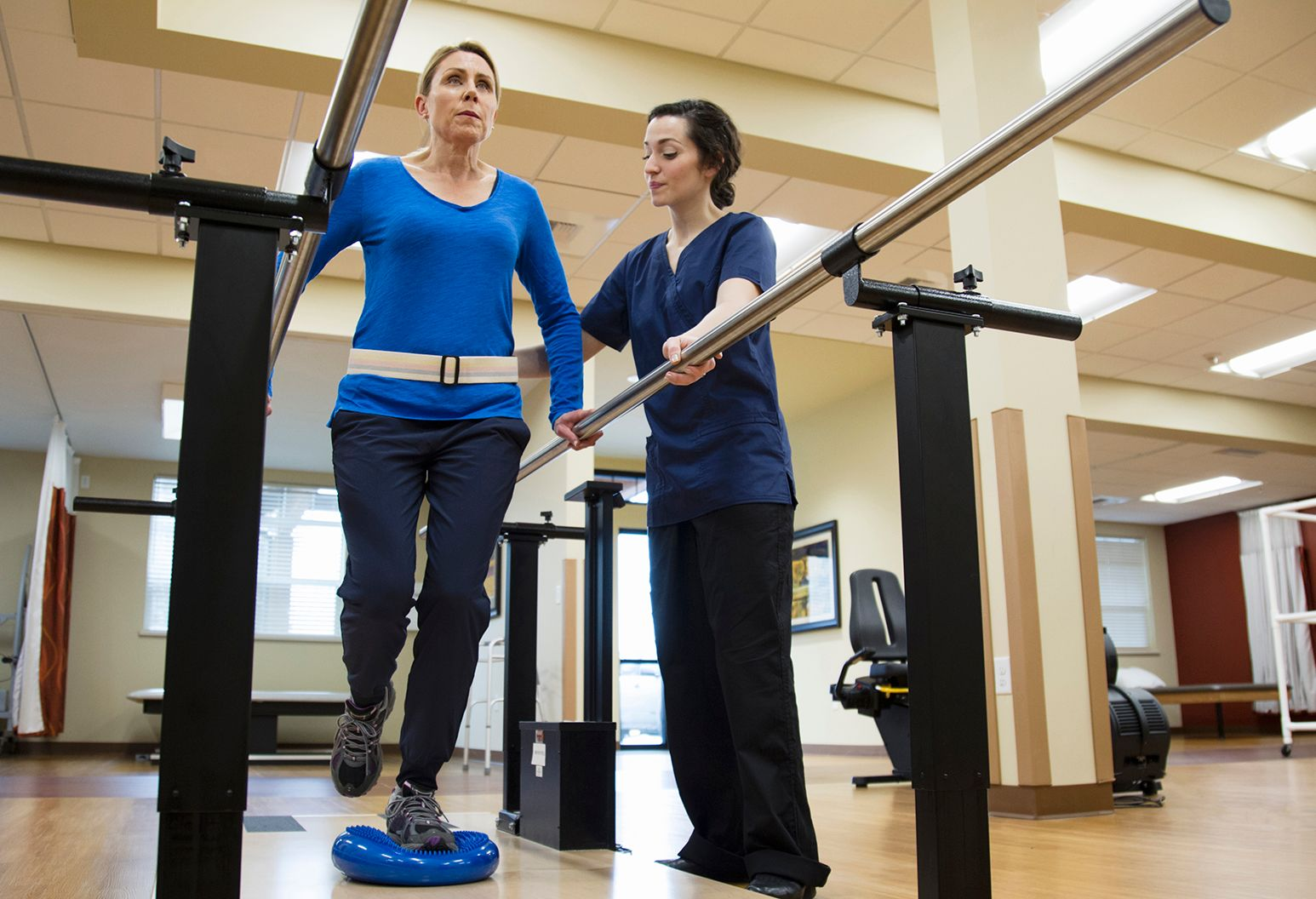 Doctor helping weak patient walk in a physical therapy session.