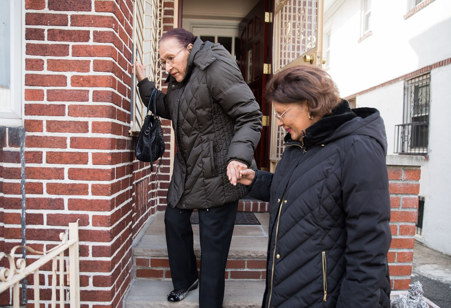 Woman helps older woman walk down the stairs as they leave a home.