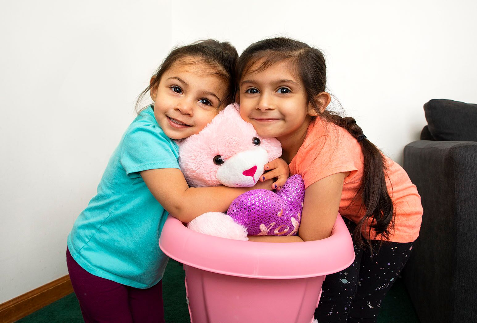 Two young girls with dark hair hugging a teddy bear.