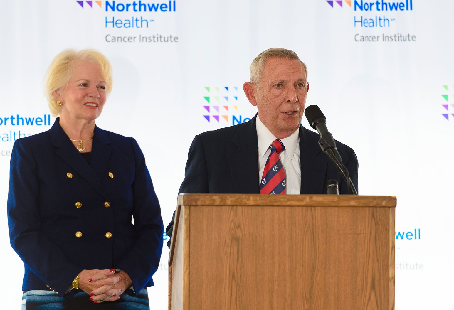 An older man in a suit stands in front of a podium and is speaking into a microphone as an elderly woman dressed in a blue blazer stands beside him smiling. She has blonde hair and is wearing gold earrings, a gold anchor necklace, and a gold bracelet.