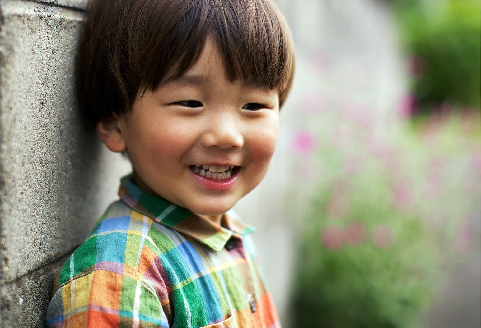 A toddler boy wearing a multicolored plaid shirt stands against a concrete wall outside and smiles.