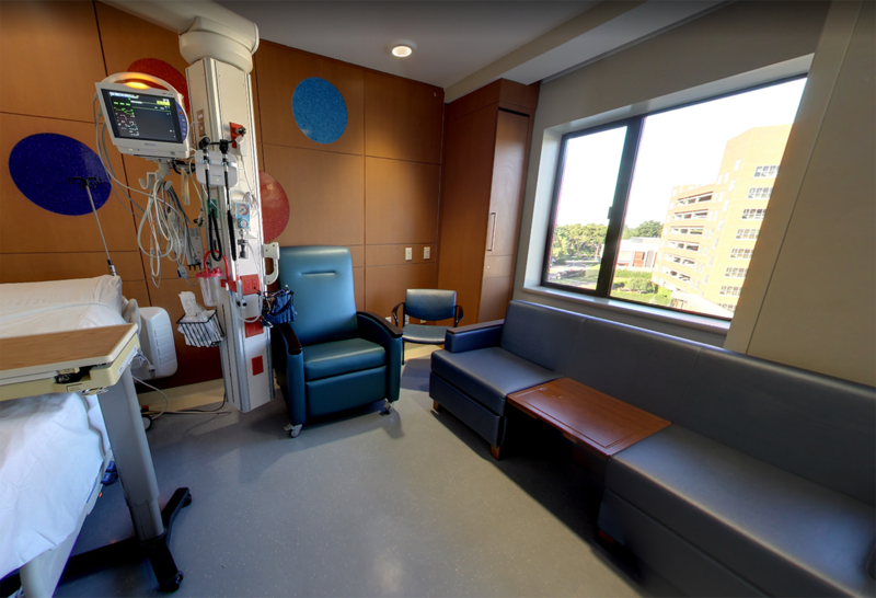 This is a patient room in the stem cell transplant until with a sleeper bed and private bathroom. The brown walls feature large colorful circles decorating them, and there is a large window.