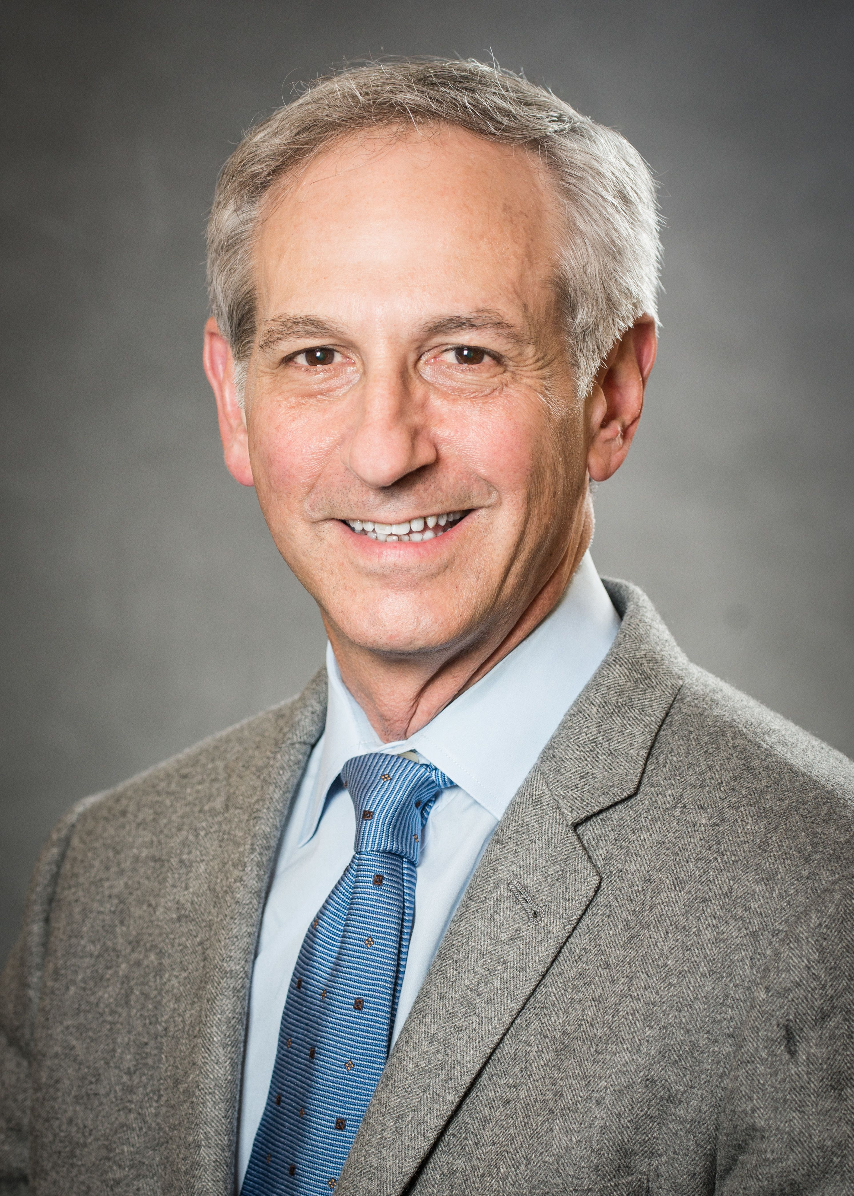 Mark Schiffer, MD, wearing a blue tie and a grey jacket