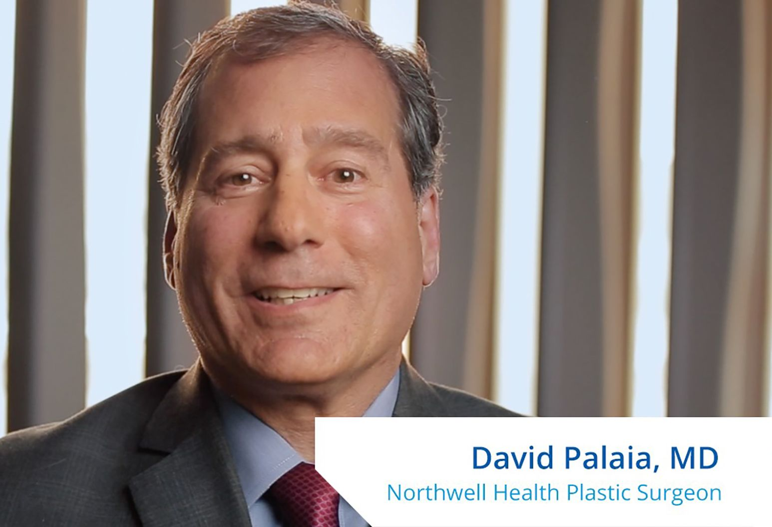 """A man with short black and gray hair speaks to the camera. On the lower right corner of the photo it reads, """"David Palaia, MD. Northwell Health Plastic Surgeon."""""""