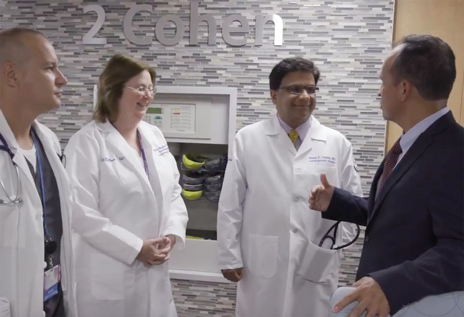 Two male doctors and one female doctor in white coats speak to a man in a suit.