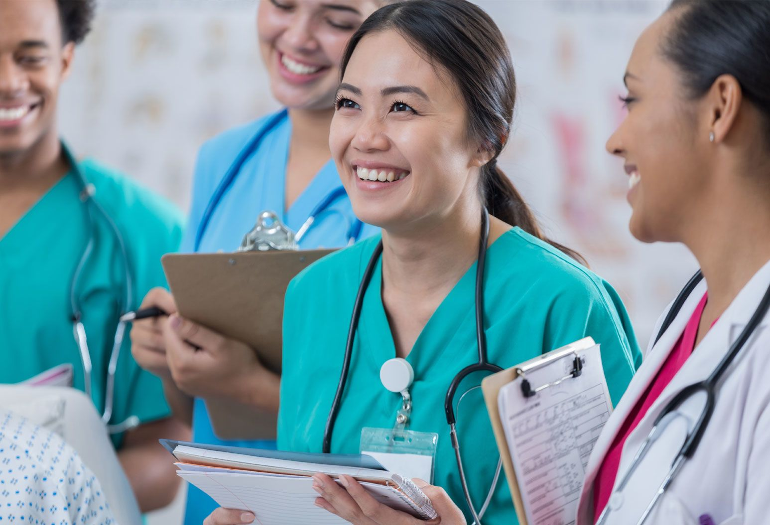 A group of people in scrubs hold clipboards. The focus is on a young asian woman who is smiling and looking up.